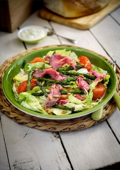 Styled photograph of a beef salad on a green plate