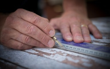 Close up of man with ruler and knife making precise cuts