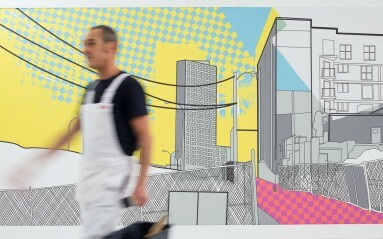 Photo of man in overalls walking away from a digital wallcovering