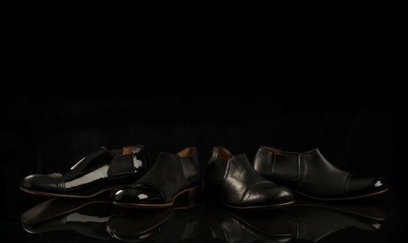 Styled photograph of mens black shoes photographed against a black backrgound
