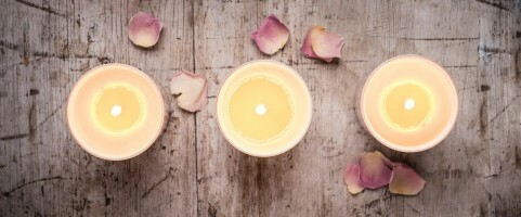 Styled shot of candles on a wooden board with scattered petals
